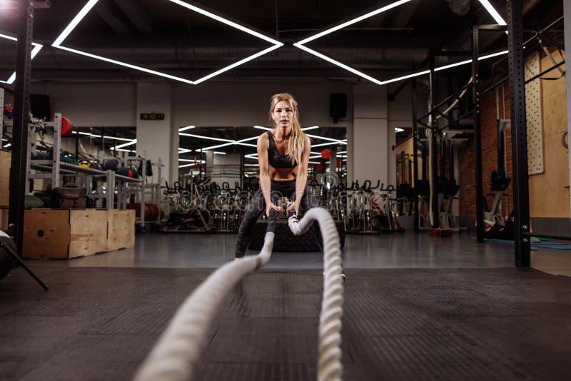 A mulher apta do gorgeouse está dando certo com cordas da batalha para manter o ajuste foto de stock royalty free