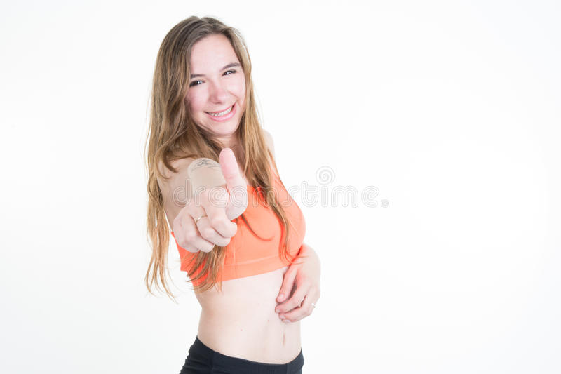Mulher apta dos jovens do sorriso que gesticula o polegar acima, isolado no branco foto de stock