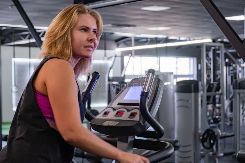 Mulher apta dos jovens no gym Exercício fêmea com cr elíptico fotos de stock