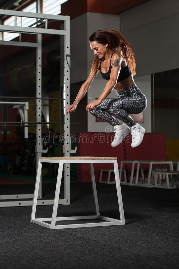A mulher apta dos jovens que faz a caixa salta no Gym imagens de stock royalty free