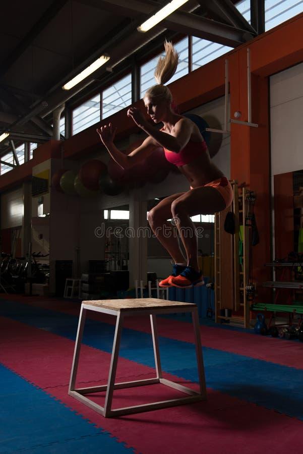 A mulher apta dos jovens que faz a caixa salta no Gym imagem de stock