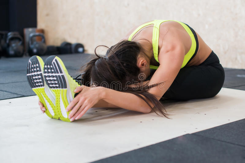 Mulher apta dos jovens que faz o exercício dianteiro assentado da dobra, esticão fêmea desportivo foto de stock royalty free