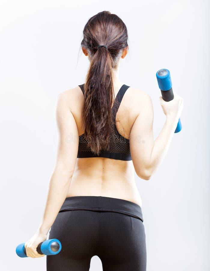 Mulher apta durante o exercício com pesos, vista traseira imagem de stock royalty free