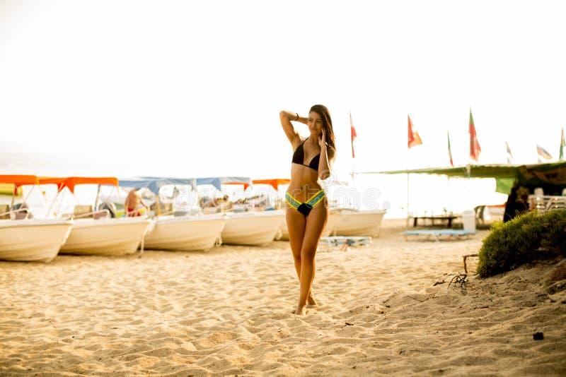Mulher apta e desportiva no roupa de banho que relaxa em uma praia no verão imagens de stock
