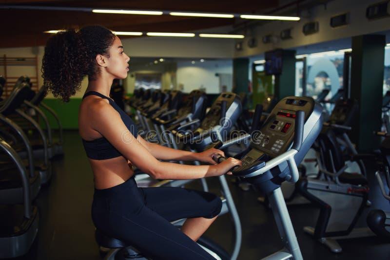 Mulher apta em uma classe da rotação no gym fotografia de stock