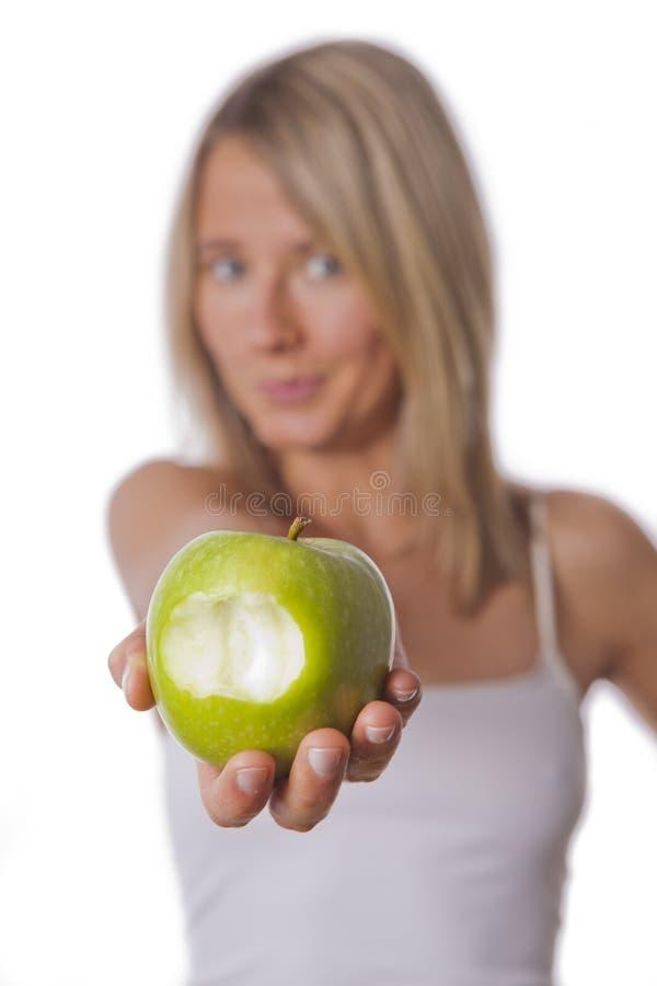 A mulher apta mostra a maçã foto de stock