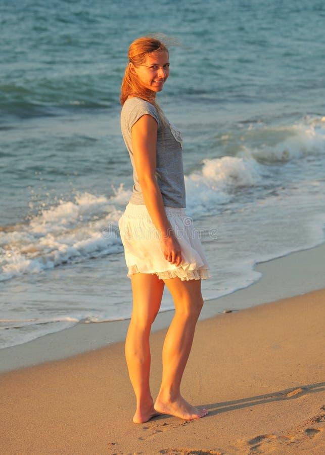 Mulher apta nova na saia curto do verão, andando em nivelar a praia, olhando sobre seu ombro, luz que brilha, mar do por do sol d imagens de stock royalty free