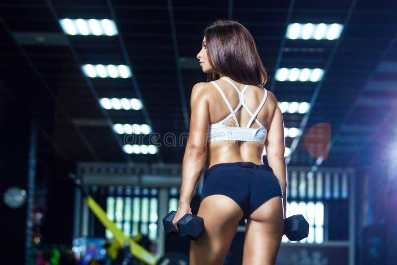 Mulher apta nova no short desportivo e em pesos guardando superiores ao estar na opinião traseira do gym imagem de stock