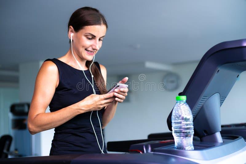 Mulher apta nova que corre na escada rolante que escuta a m?sica atrav?s do fones de ouvido no gym fotografia de stock