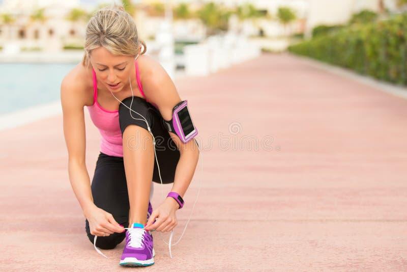 Mulher apta que amarra a sapata dos esportes antes do exercício da manhã imagens de stock royalty free
