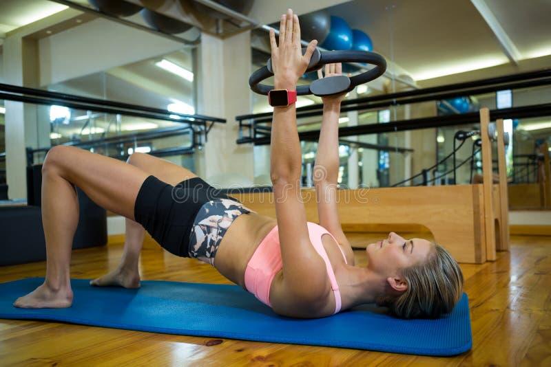A mulher apta que exercita com pilates soa na esteira fotografia de stock
