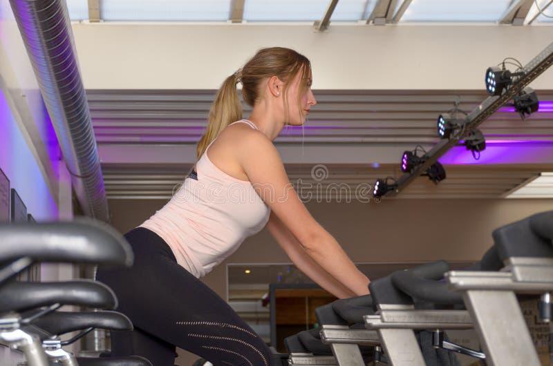 Mulher apta que exercita na bicicleta estacionária no gym imagem de stock