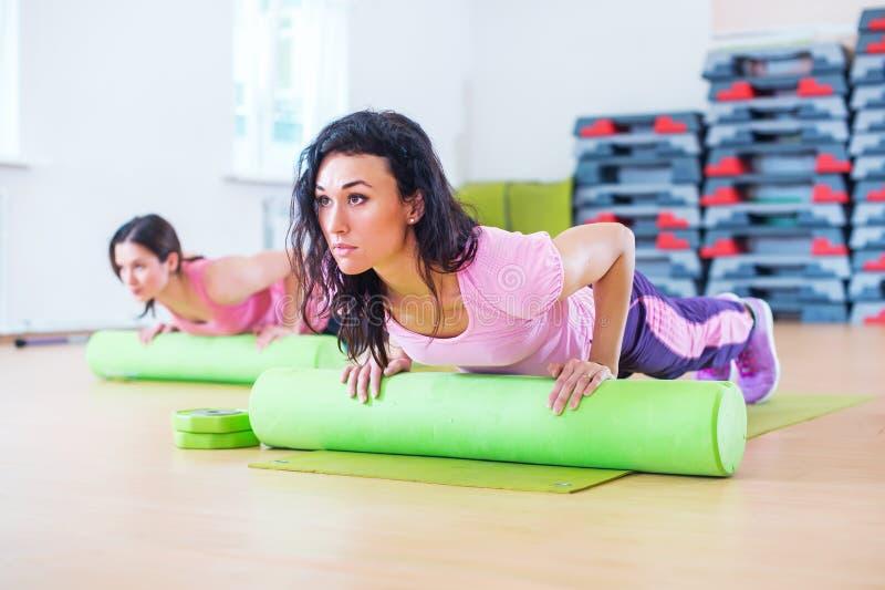 A mulher apta que exercita no assoalho que usa fazer do rolo da espuma empurra levanta o exercício do tríceps imagens de stock royalty free
