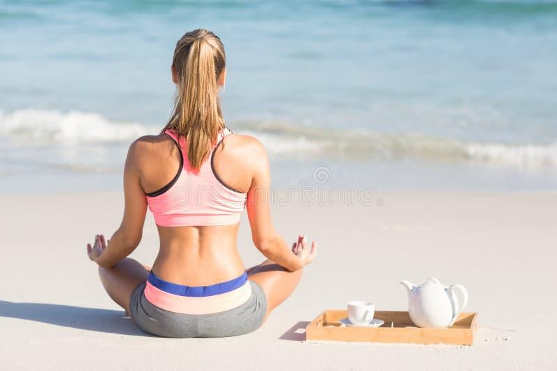 Mulher apta que faz a ioga ao lado do mar fotografia de stock