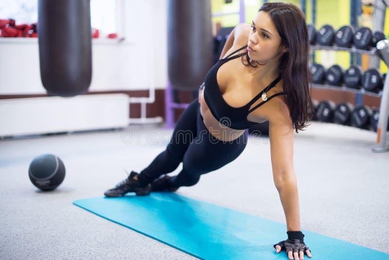 Mulher apta que faz o conceito lateral da pose da ioga da prancha fotografia de stock