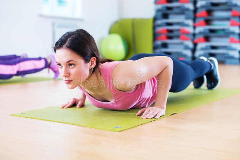 A mulher apta que faz o exercício da prancha e empurra levanta o trabalho no tríceps dos músculos abdominais foto de stock