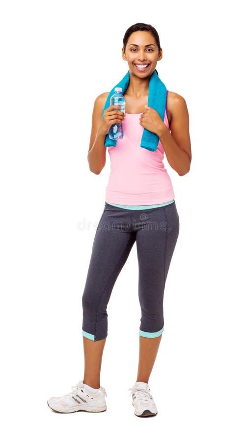 Mulher apta que guarda a garrafa de água e a toalha imagem de stock