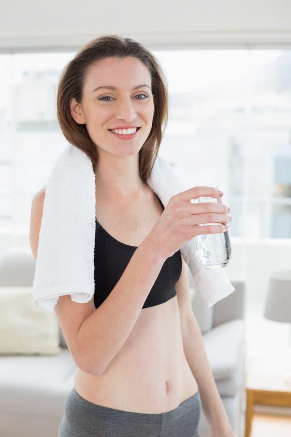 Mulher apta que guarda a garrafa de água no estúdio da aptidão imagens de stock