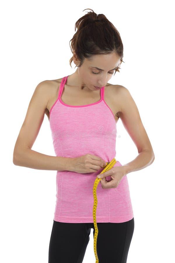 Mulher apta que mede sua cintura com uma fita imagem de stock