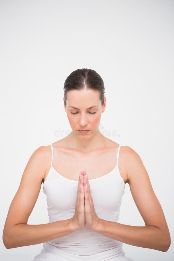 Mulher apta que medita com as mãos cruzadas fotos de stock