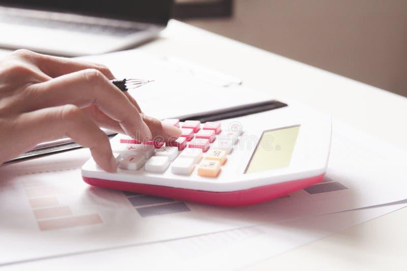 Mulher ascendente fechado que calcula sobre o relatório da finança no escritório fotos de stock royalty free