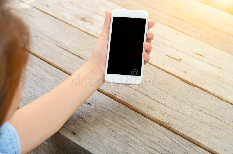 Mulher ascendente próxima da mão que guarda e que usa o telefone com a tela vazia na tabela de madeira fotografia de stock royalty free