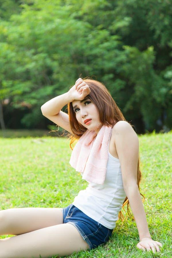 A mulher asiática é assento cansado no gramado. imagens de stock