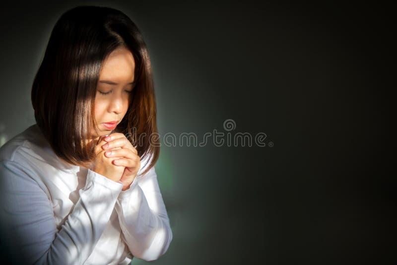 A mulher asiática adulta média que senta e que guarda as mãos para implora foto de stock royalty free