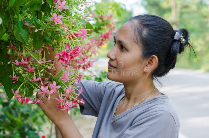 A mulher asiática aprecia com as flores no jardim imagens de stock royalty free