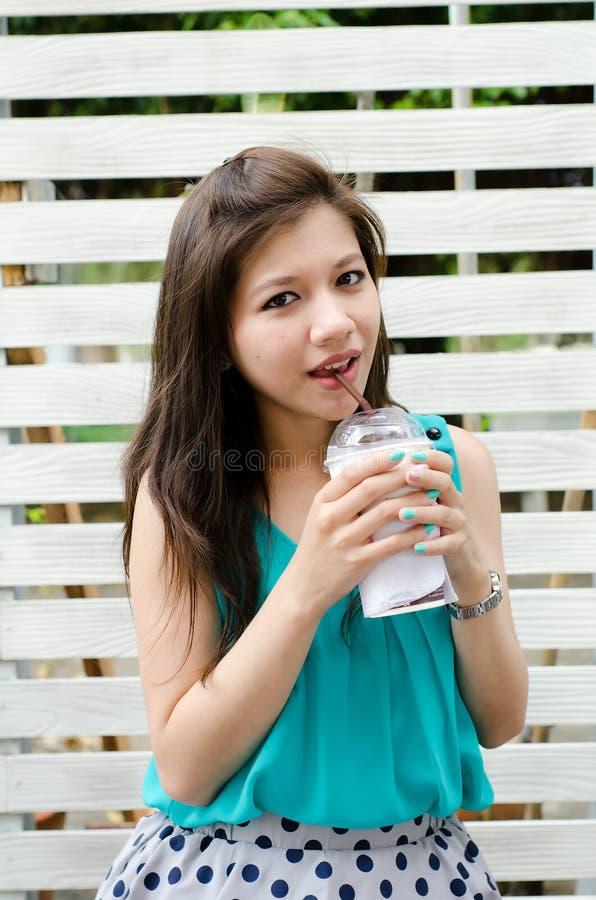 A mulher asiática atrativa aprecia sua bebida imagens de stock royalty free