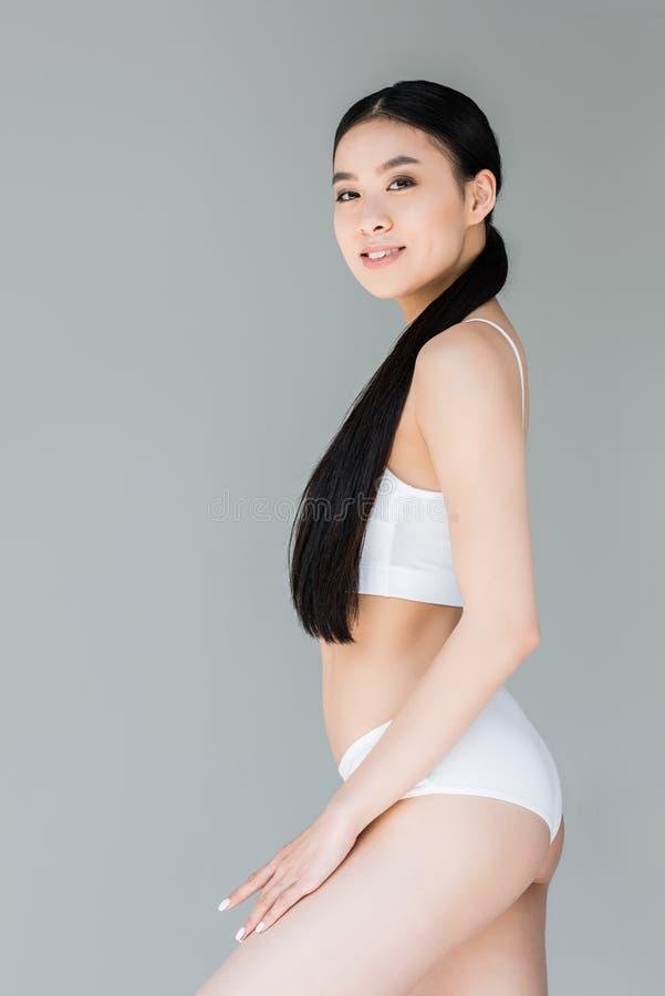 mulher asiática atrativa na roupa interior branca que levanta no cinza fotografia de stock