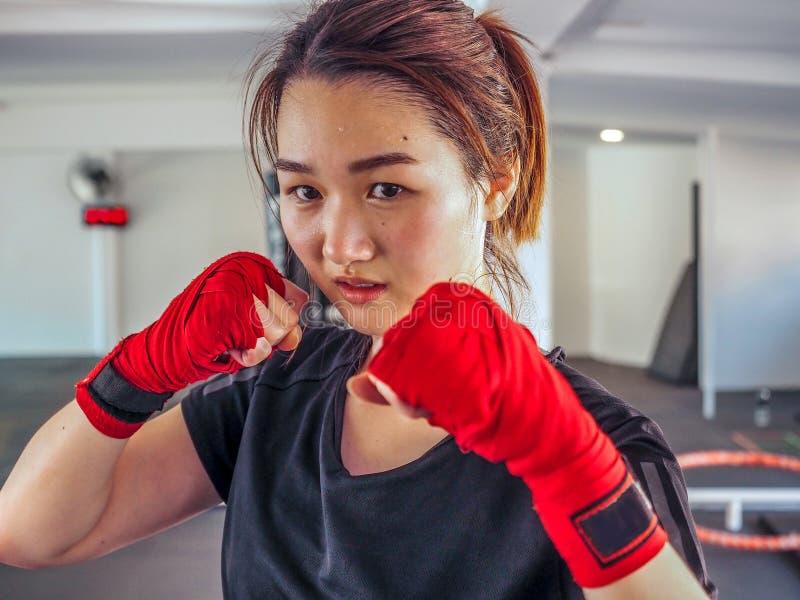 A mulher asiática atrativa nova com luvas de encaixotamento está pronta para a batalha fotografia de stock
