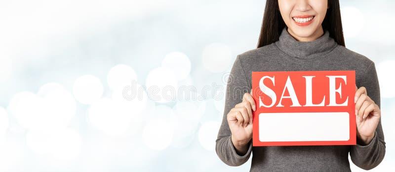 Mulher asiática atrativa nova que guarda o cartão do quadro indicador da venda que mostra para o preço imagem de stock
