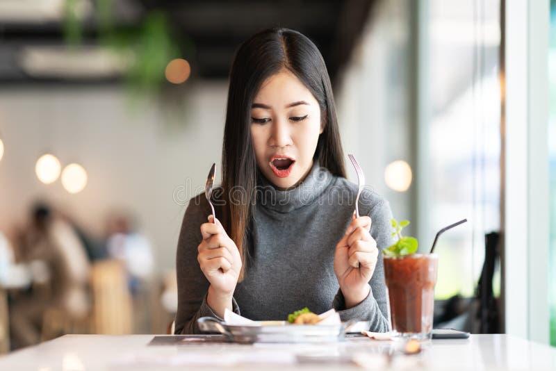 Mulher asiática atrativa nova que guardam a forquilha e colher que sente com fome, entusiasmado foto de stock