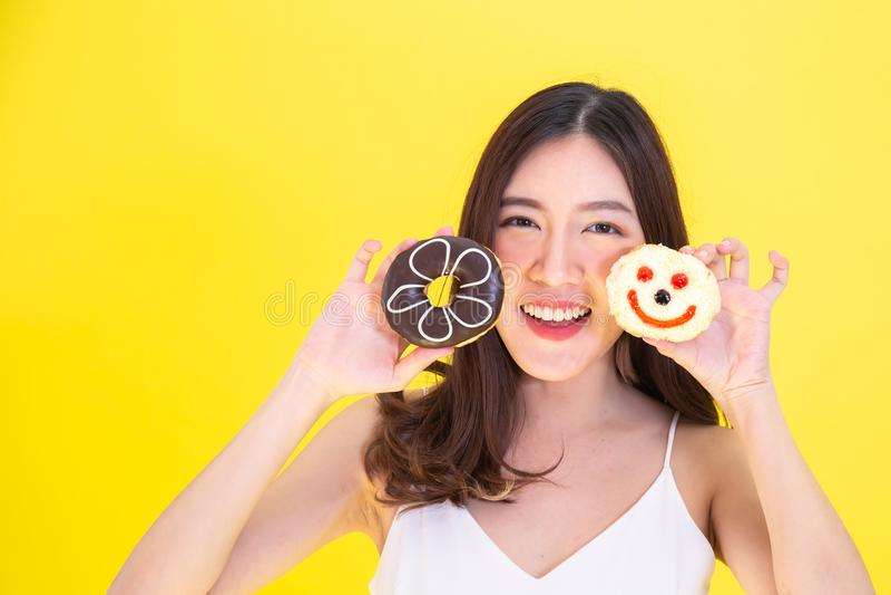 Mulher asiática atrativa que guarda dois anéis de espuma com expressão de sorriso bonito sobre o fundo amarelo fotografia de stock