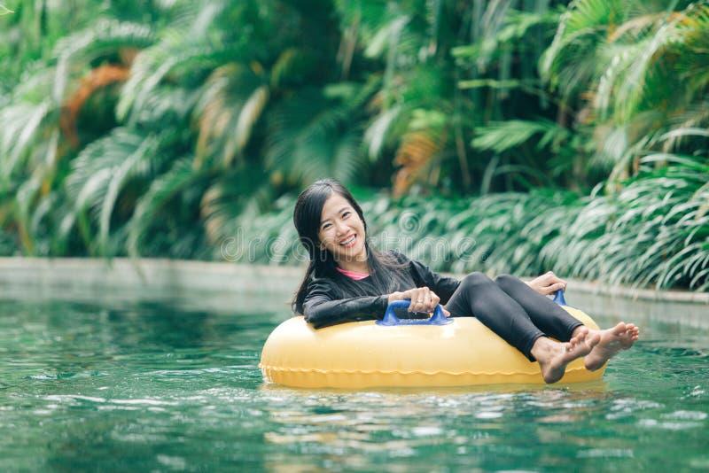 Mulher asiática atrativa que relaxa na associação do rio fotografia de stock