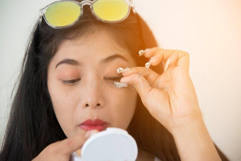 A mulher asiática bonita cola as pestanas falsas dsi mesma Retrato do close up imagem de stock royalty free