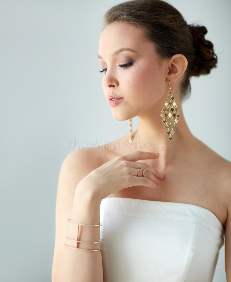 Mulher asiática bonita com brincos e bracelete foto de stock royalty free