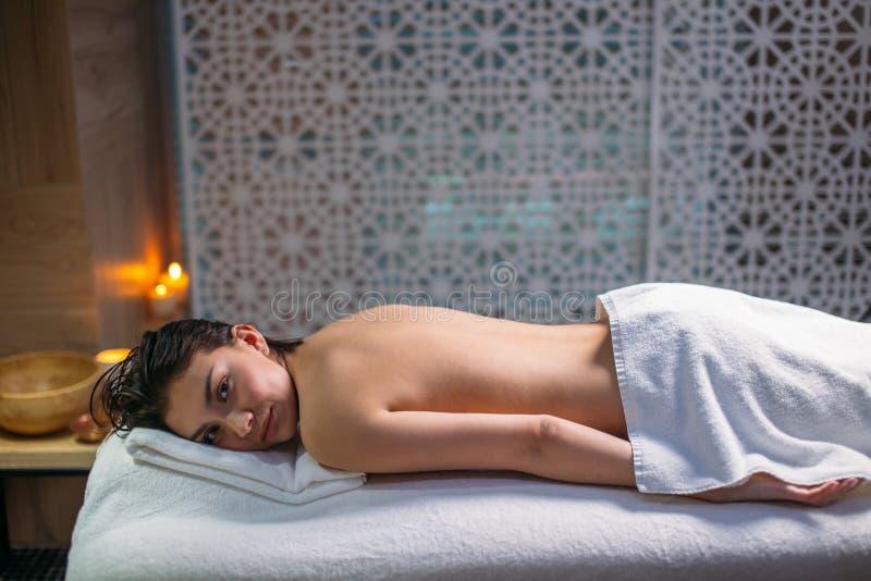 Mulher asiática bonita com o cabelo preto que encontra-se na cama no salão de beleza dos termas imagens de stock