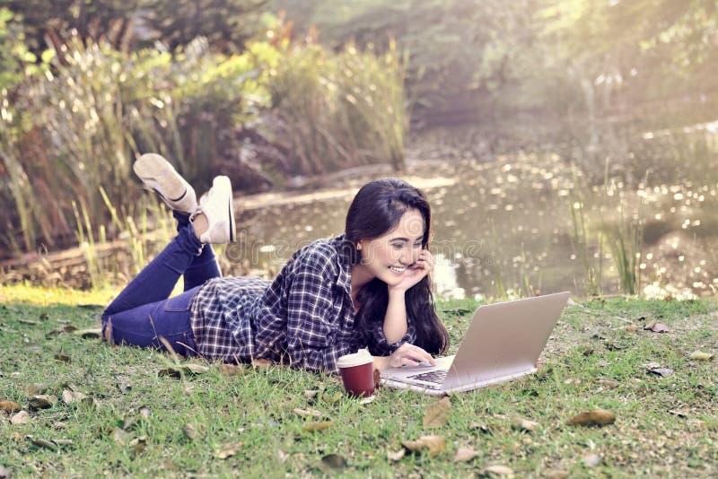 Mulher asiática bonita com o portátil que encontra-se na grama verde imagens de stock