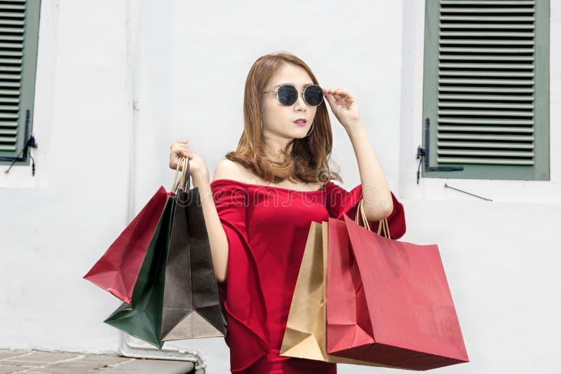 Mulher asiática bonita com os óculos de sol que levam sacos de compras imagens de stock royalty free