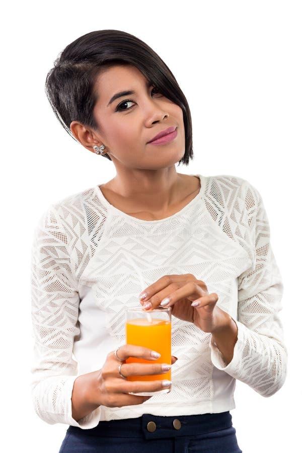 Mulher asiática bonita com vidro do suco de laranja Tiro do estúdio foto de stock royalty free