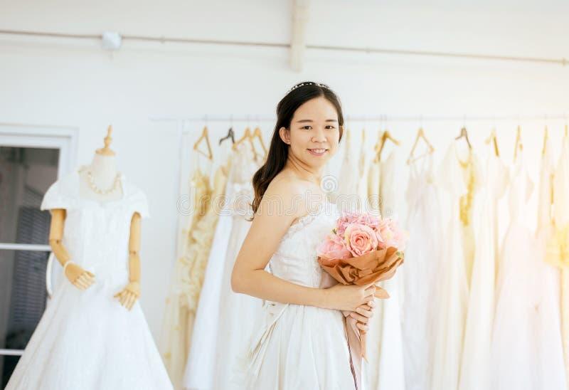 Mulher asiática bonita da noiva que guarda um ramalhete disponível para o casamento com sorriso e momento feliz, romântico e doce imagens de stock