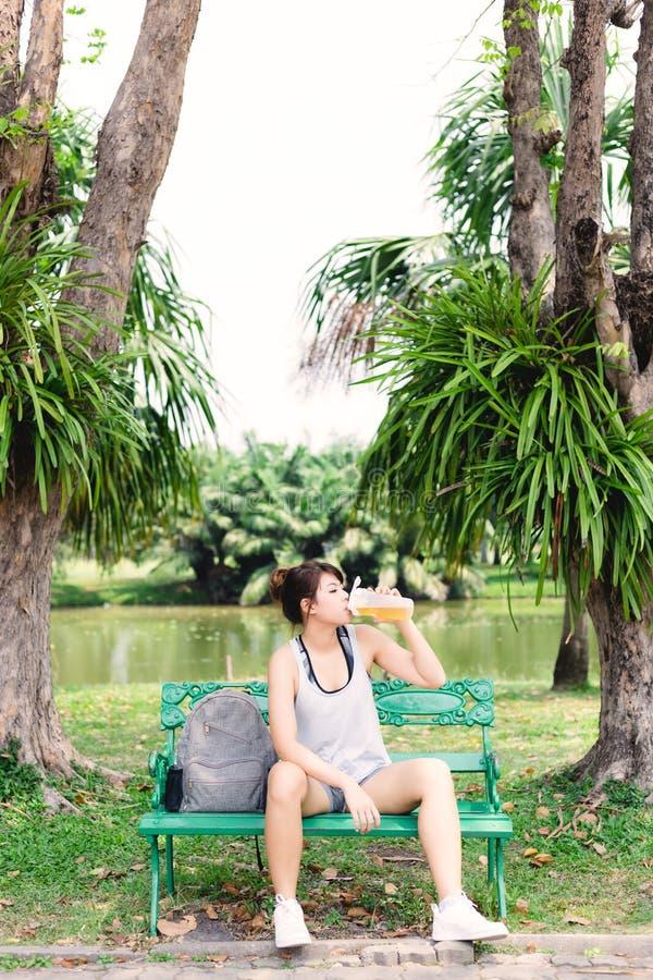 A mulher asiática bonita de encantamento obtém dia ensolarado sedento, dos it's e tempo quente A menina bonita toma um resto e  imagem de stock