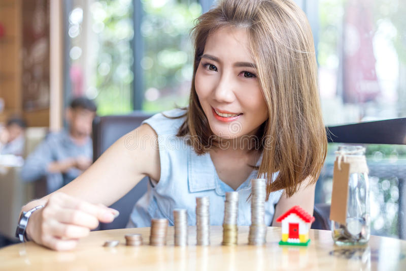 Mulher asiática bonita de sorriso que empilha moedas de ouro fotos de stock royalty free