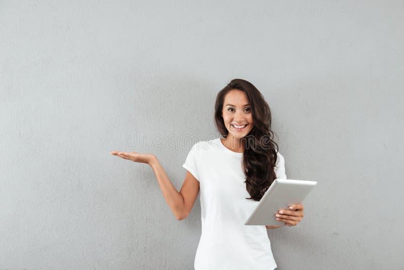 Mulher asiática bonita de sorriso que guarda o tablet pc fotografia de stock