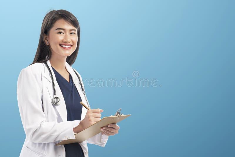 Mulher asiática bonita do doutor com notas da escrita do revestimento do laboratório na prancheta imagens de stock