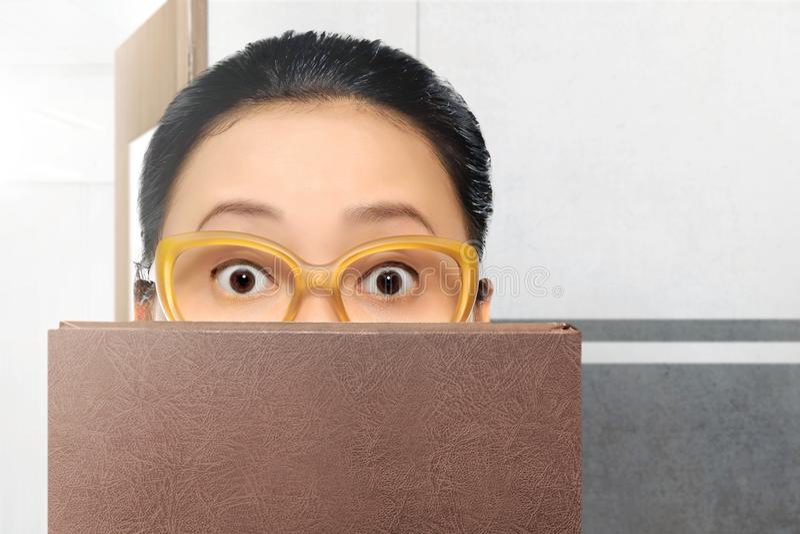 Mulher asiática bonita do estudante com monóculos e livro imagem de stock royalty free