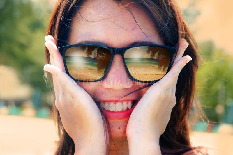 Mulher asiática bonita e feliz que sorri guardando seus óculos de sol vestindo da cara com reflexão tropical do mar e da palmeira fotografia de stock
