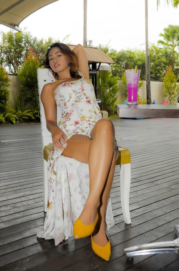 Mulher asiática bonita e 'sexy' nova no vestido à moda na cafetaria ou no restaurante do recurso de feriado que bebe o suco de fr foto de stock royalty free